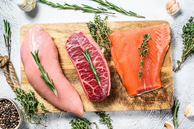 Различные виды сырого мяса на разделочной доске с зеленью. лопатка из говядины, филе лосося и грудка индейки. стейки. белый фон. вид сверху.