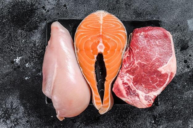 Различные виды стейков из сырого мяса стриплоин из говядины, лосось и куриная грудка. черный фон. вид сверху.