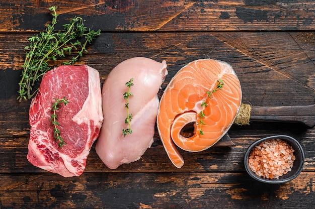 Различные виды стейков из сырого мяса стриплоин из говядины, лосось и куриная грудка. темный деревянный фон. вид сверху.
