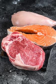 さまざまな種類の生肉ステーキビーフサーロイン、サーモン、鶏の胸肉。上面図。 Premium写真