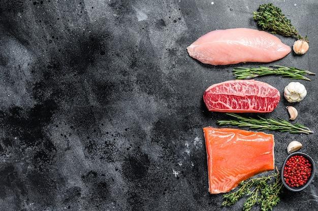 Различные виды сырого мяса с зеленью. лопатка из говядины, филе лосося и грудка индейки. стейки. черный фон. вид сверху. скопируйте пространство.