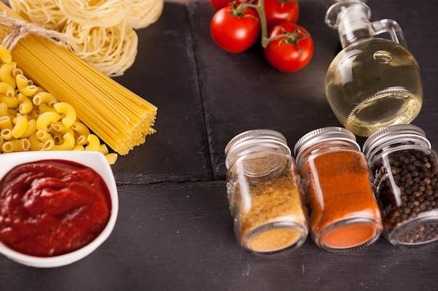 ひまわり油、スパイス、暗いヴィンテージの背景にトマトソースのボウルの横にあるさまざまな種類の生パスタ