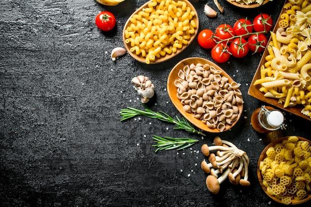 Различные виды сырой пасты в мисках с грибами, розмарином и помидорами.