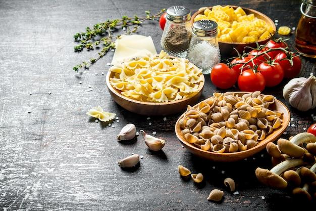 소박한 테이블에 토마토, 마늘, 버섯이 든 그릇에 다양한 종류의 생 페이스트