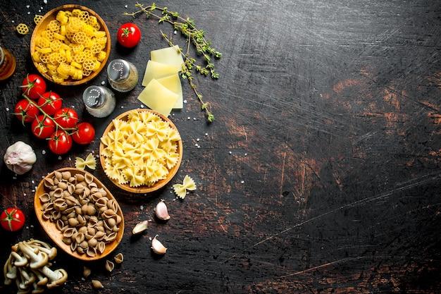 Различные виды сырой пасты в мисках с помидорами, чесноком и грибами.