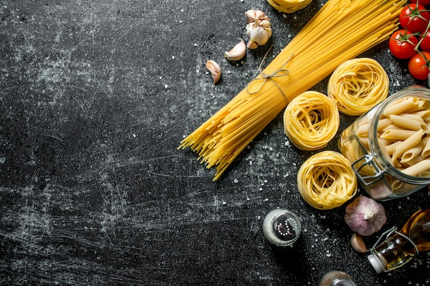 Различные виды сырых паст с маслом, помидорами и специями. на черном деревенском фоне