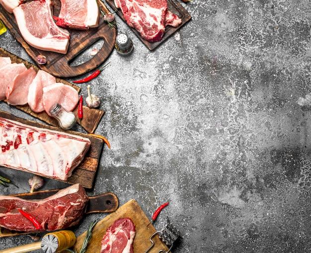さまざまな種類の生の豚肉と牛肉にスパイスとハーブを添えました。素朴な背景に。