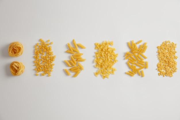 Различные виды сырых сырых макарон на белом фоне. гнезда из макарон, фарфалле, триполини, пенне, фузилли можно использовать для соусов или блюд. разнообразие итальянского продукта. разные формы. концепция питания