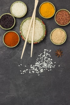 Различные виды риса и сухих специй в мисках. бамбуковые палочки. плоская планировка.