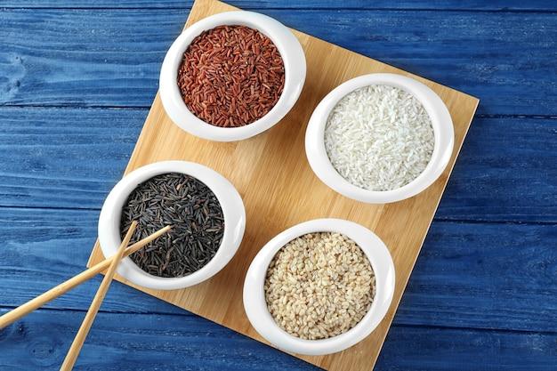 Различные виды риса в мисках на деревянном подносе, вид сверху