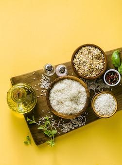 Разные виды риса на деревянной доске из оливкового дерева. с листьями базилика и оливковым маслом. здоровая домашняя кухня