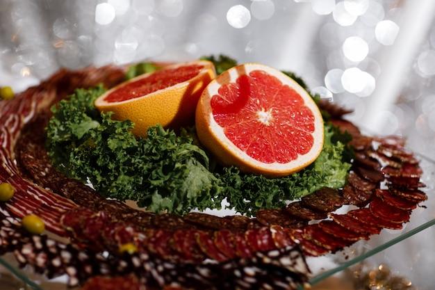 Разные виды колбас с грейпфрутом и листьями салата подаются на стеклянном подносе, плоско лежат.