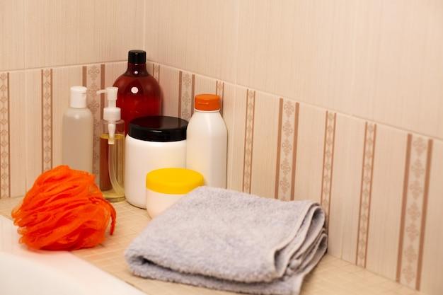 バスルームにあるさまざまな種類のシャンプー、ヘアマスク、ミセルオイル、バスタオル