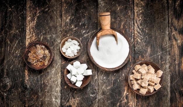 ボウルにさまざまな種類の砂糖。木製の背景に。