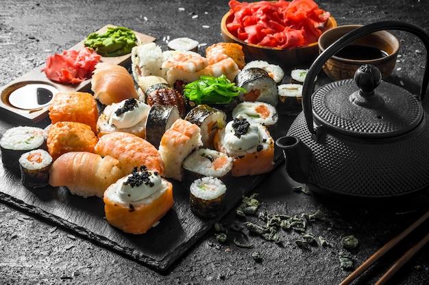 黒の素朴なテーブルにさまざまな種類の寿司、巻き寿司、醤油、生姜、緑茶を添えたロール