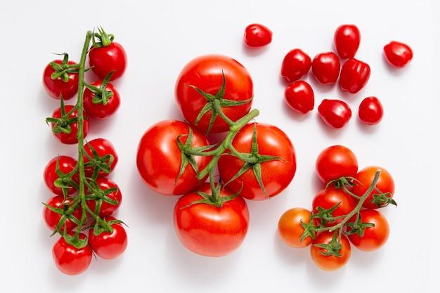 Различные виды помидоров на белом фоне. вид сверху свежих овощей.