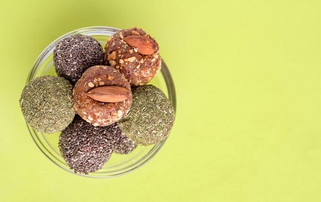 Различные виды полезных сладких конфет из сухофруктов энергетические шарики на зеленом