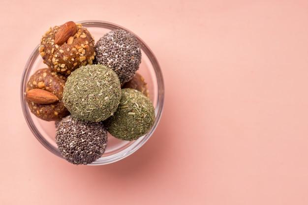 Разные виды полезных сладких конфет из сухофруктов энергетические шарики на розовом