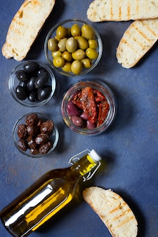 Different types of olives, bruschetta, sun-dried tomatoes and olive oil. mediterranean snacks. top view.