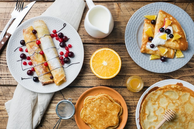 Different types of pancakes with berries on a wooden table
