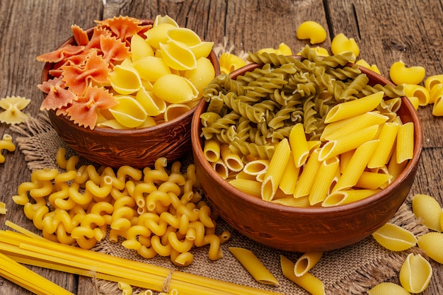 Different types of pasta in ceramic bowls. traditional italian food, healthy eating concept. rustic wooden table