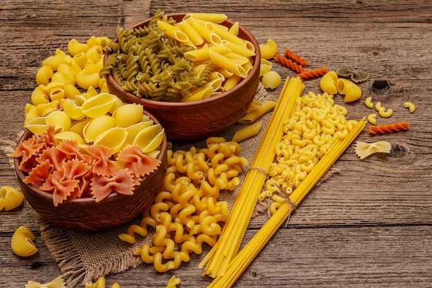 Different types of pasta in ceramic bowls
