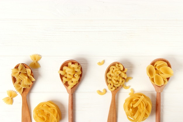 Different types of pasta closeup on a colored background