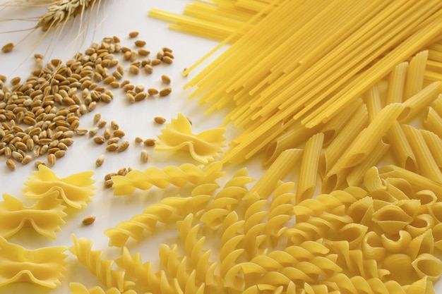 Different types of pasta. ears of wheat. white background