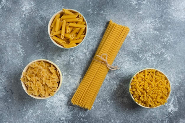 Different types of pasta on gray.