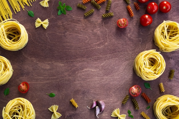 Different types of pasta on a wooden background