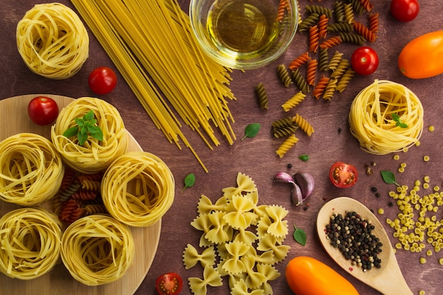 Different types of pasta on a wooden table.