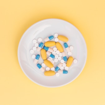 Different types of pills on white plate over yellow background