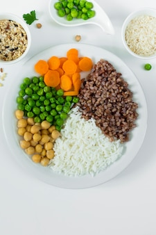 Different types of porridge with vegetables on big plate with rice bowls