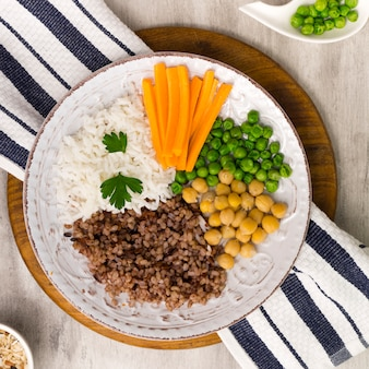 Different types of porridge with vegetables on big wooden board