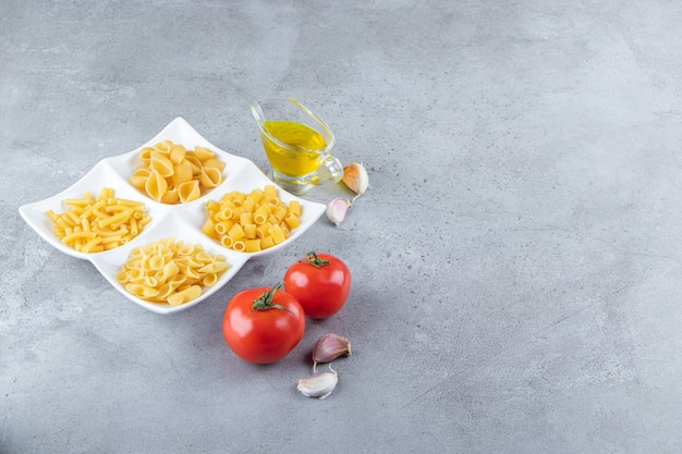 Different types of raw dry pasta with fresh red tomatoes and oil on a stone background.