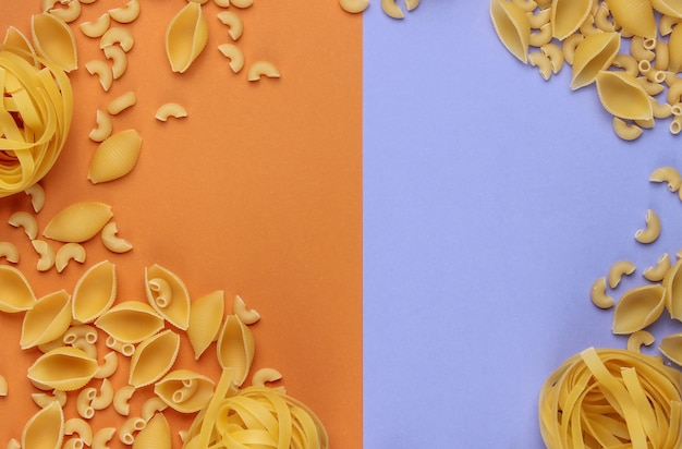 Different types of raw italian pasta on brown purple background.