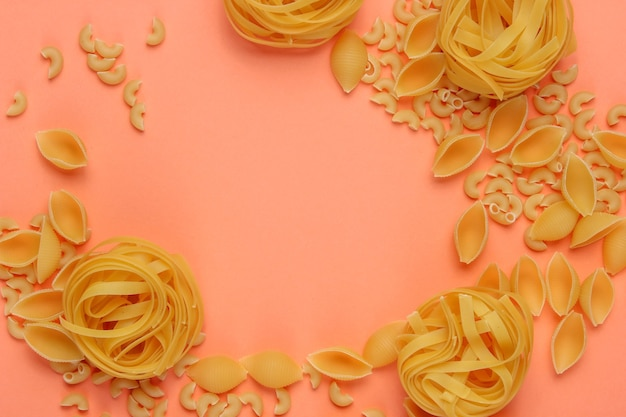 Different types of raw italian pasta on coral color background.