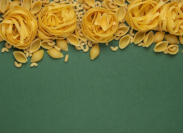 Different types of raw italian pasta on green background. top view. copy space