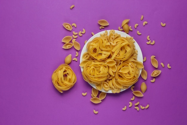 Different types of raw italian pasta in plate on purple background. top view.