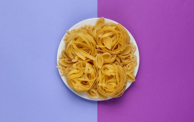 Different types of raw italian pasta in plate on purple background.