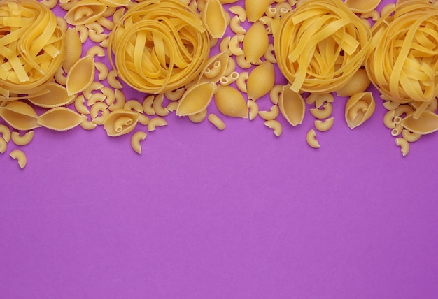 Different types of raw italian pasta on purple background. top view. copy space