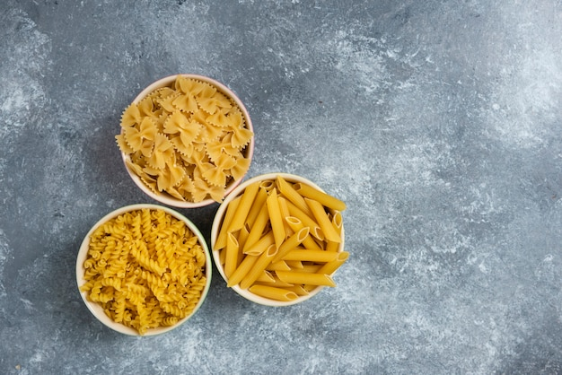 Different types of raw macaroni on marble.