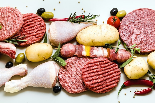 Different types of raw meat: chicken thighs, pork and beef burgers, ribs and kebabs, turkey meatballs, ready to be cooked with potatoes, hot pepper, olives and black olives and aromatic herbs