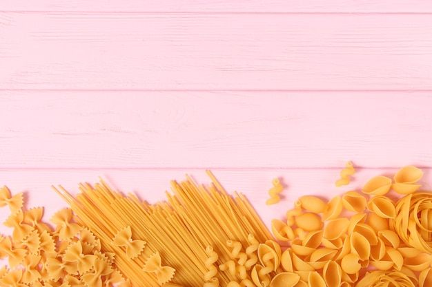 Different types of raw pasta closeup on a colored background