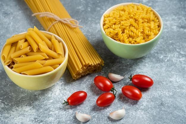 Diversi tipi di pasta cruda con verdure.