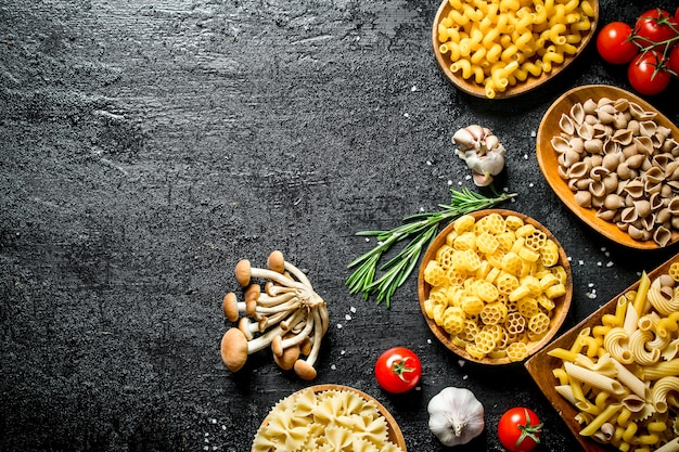 Different types of raw paste in bowls with mushrooms, rosemary and tomatoes. on black rustic background