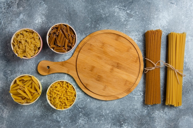 Different types of raw spaghetti with wooden board.