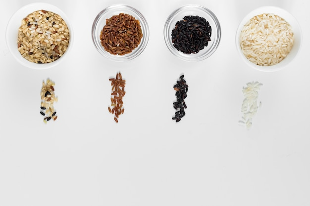 Different types of rice in bowls on light table