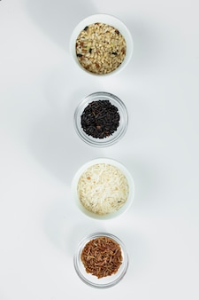 Different types of rice in bowls on table
