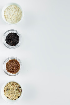 Different types of rice in bowls on white table